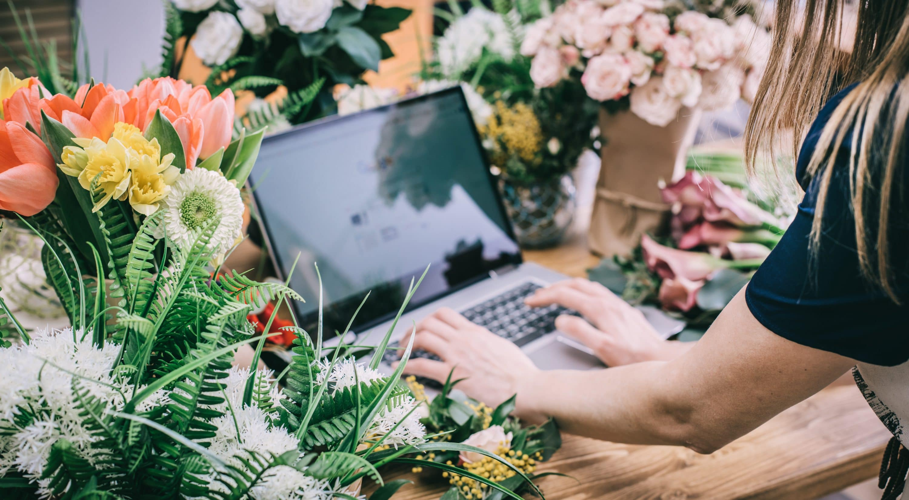 small local florist updates her website on laptop surrounded by flowers, Dentons Digital, Website Design, Wiltshire, Somerset