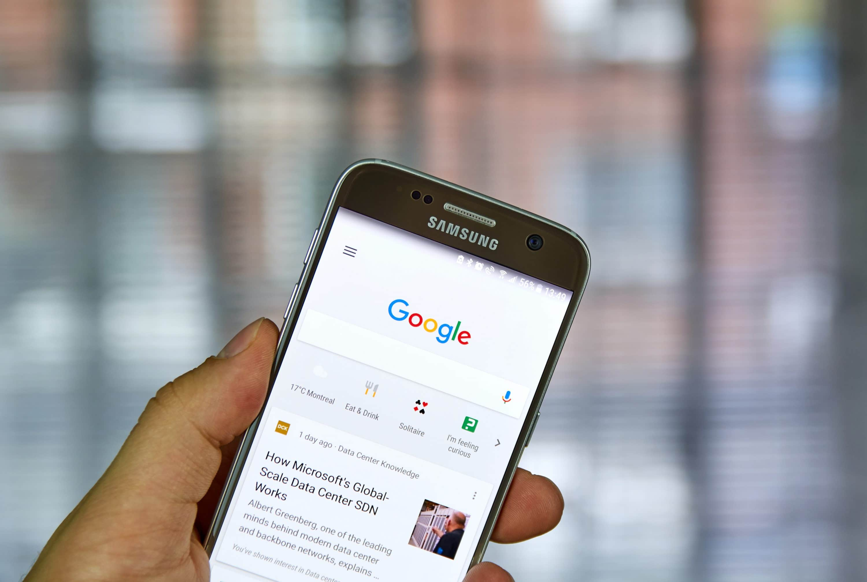 Hand holding mobile phone showing google search page, Dentons Digital, Wiltshire, Somerset