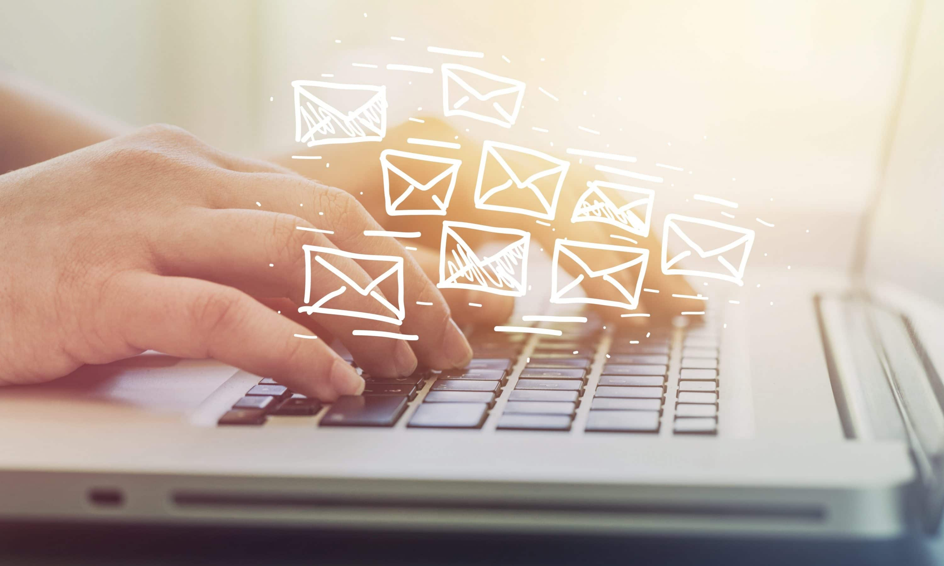 Hands typing on laptop with email icons floating, Email Marketing, Dentons Digital, Website Design, Wiltshire, Somerset