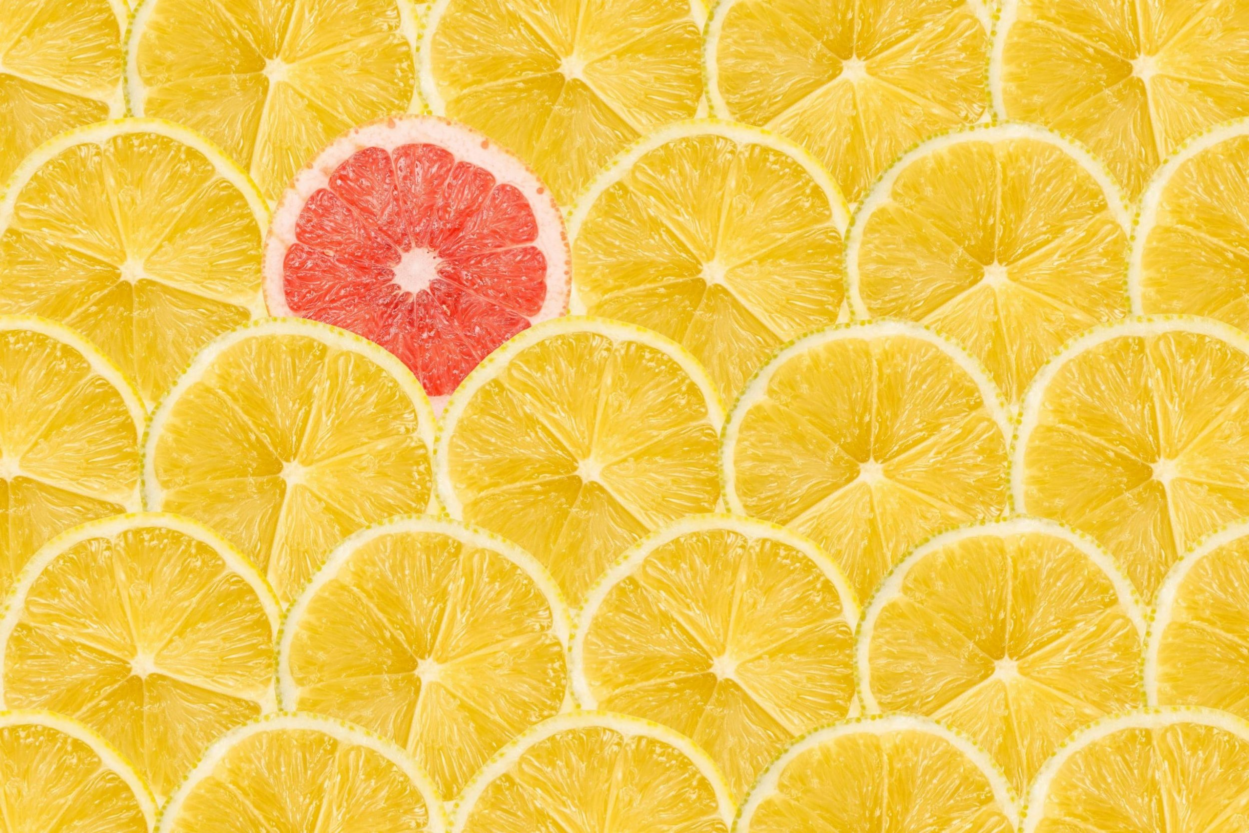 Pink grapefruit stands out from the crowd of lemons.